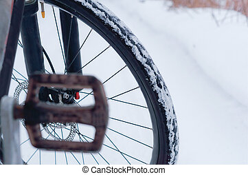 Bicycle wheel on snow-covered road background