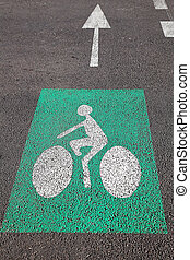 Arrow and bike lane sign at asphalt reserved for bicycles