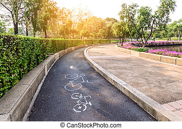 Bike lane with bicycle sign in urban park with sunlight.