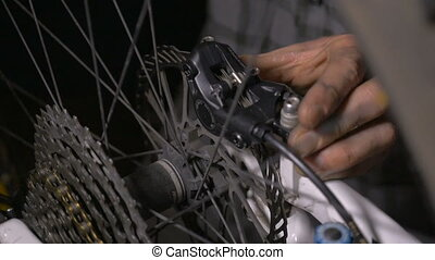 Bike mechanic making adjustments to the disc brakes of a...