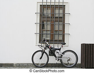 Conceptual shot of a bycicle resting on a white wall.