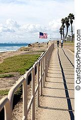 Couple riding bicycles along bike path in at Huntington Beach, California