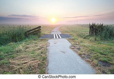 bike path on countryside at misty sunrise