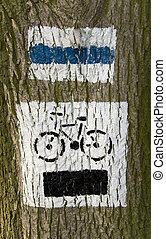Bike path sign on tree