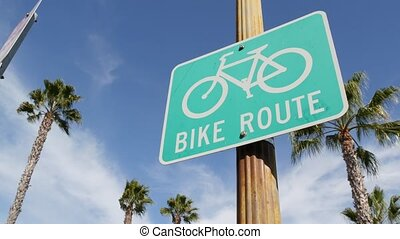 Bike Route green road sign in California, USA. Bicycle lane singpost. Bikeway in Oceanside pacific tourist resort. Cycleway signboard and palm. Healthy lifestyle, recreation and safety cycling symbol
