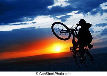 Bike - Man doing bicycle juggle on sunset background