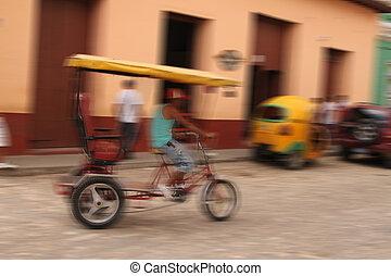 Bike taxi driving along a Cuban street with motion blur