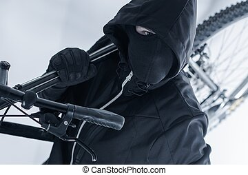 Bike Theft. Bike Thief in a Hood, Black Mask and Black...