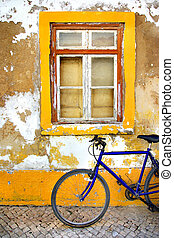 Bicycle in front of a window of a old white and yellow house