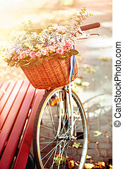 Bike with basket of spring flowers in Park.