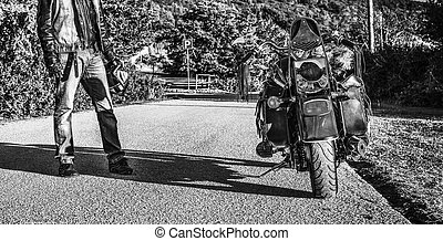 Biker and classic motorcycle at sunset in black and white