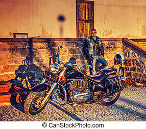 Biker and classic motorcycle at sunset
