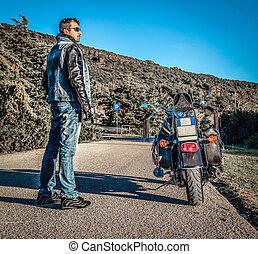 Biker and classic motorcycle on a country road