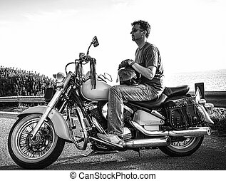 Biker and classic motorcycle parked in black and white
