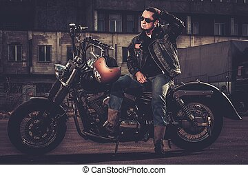 Biker and his bobber style motorcycle on a city streets