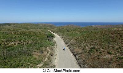 Biker biking to the beach - Aerial from a biker biking to...