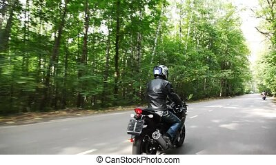 Biker catches up with other biker on road. Moving camera