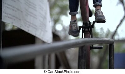 Biker doing peg grind down the hand rail over the stairs Slow Motion 400 fps