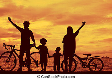 Biker family silhouette at the beach at sunet.