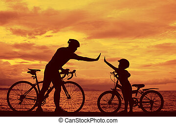 Biker family silhouette , daddy and son at the beach at...