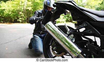Biker fastens licence plate on black motorcycle in park