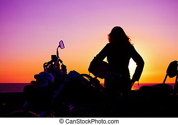 girl and classic motorcycle at sunset