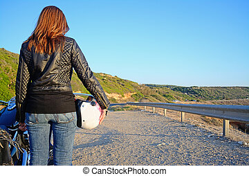 biker girl and motorcycle on the edge of the road