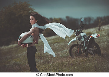 Biker girl next to a motorcycle
