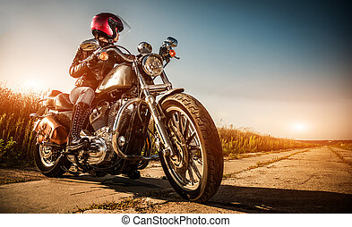 Biker girl on a motorcycle in a leather jacket and a helmet,...