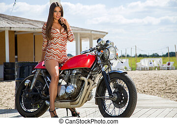Biker Girl on Retro Motorcycle - Portrait of a cool woman on...