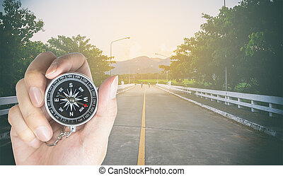 Biker holding compass on a country road for direction