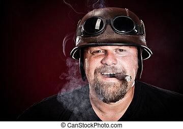 biker in a helmet smokes a cigar on a dark background