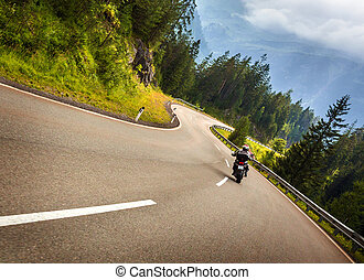 Biker in Austrian mountains riding on curve road, Alps,...