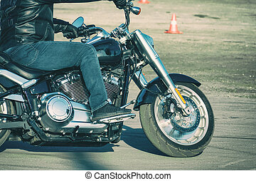 Biker in jeans riding a motorcycle