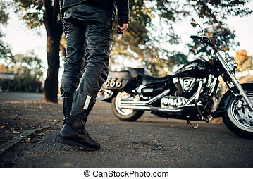 Biker in leather clothes goes to his chopper