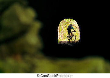 biker in mountain bike at the end of a tunnel