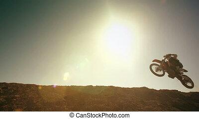 Biker Jumping Against Sun - Motocross bikers jump throw the...
