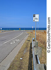 On a rural road in Stoney Creek, Ontario, a sign and markings on the street shows this is a designated lain for bicycles, background lake Ontario.