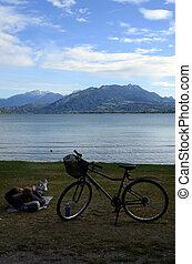 Biker Man resting on annecy lake beach, savoy, france