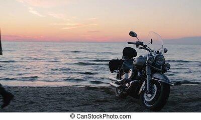 Biker motorcyclist on the ocean shore in the evening