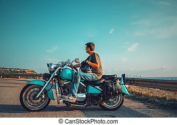 Biker on a classic motorcycle by the sea