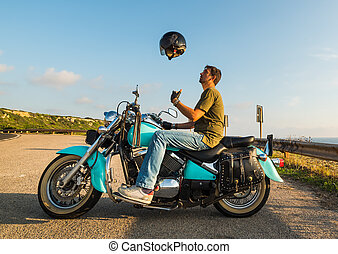 Biker on a classic motorcycle tossing the helmet in the air