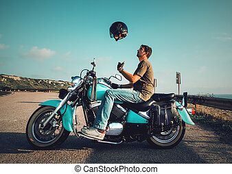 Biker on a motorcycle tossing the helmet in the air