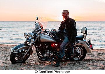 Biker on the beach at sunset