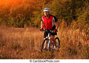 Biker on the forest road riding outdoor