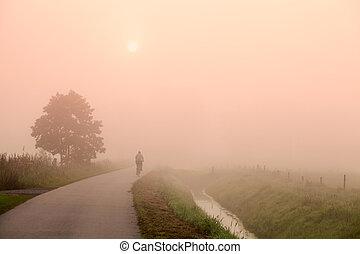 biker on the road at misty sunrise