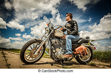 Biker in sunglasses and leather jacket on the road