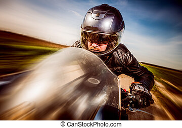 Biker racing on the road - Biker in helmet and leather...
