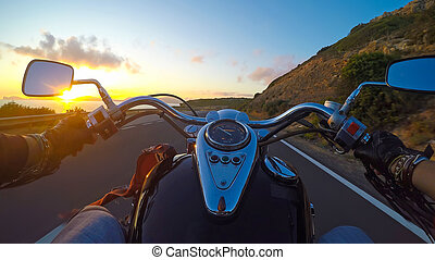 riding a classic motorcycle at sunset