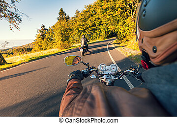 Biker riding motorcycle  in sunny morning